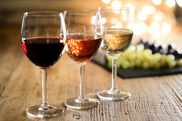 three glass of white red and rose wine with dim light in wooden restaurant table with a grape background