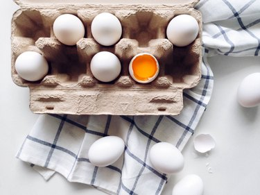 White eggs in carton with dish towel