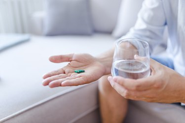 a person holding a keratin pill in one hand and a glass of water in the other hand