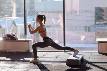 Portrait of happy young woman before training near window at gym
