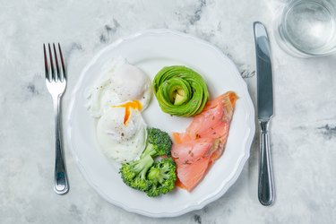 Top view of a plate with keto diet food, including salmon, eggs and avocado