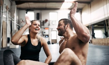 Fit young couple high fiving together after a workout