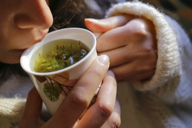 a woman drinking sage tea, as a natural remedy for cough