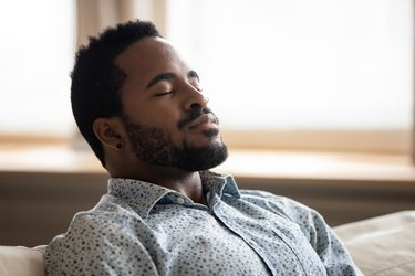 Tranquil young Black man with eyes closed breathing on couch