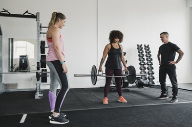 Women Deadlifting Weights with a Personal Trainer in the Gym