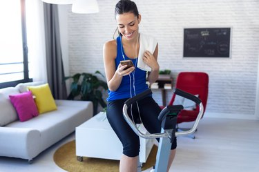 Smiling young woman using mobile phone after training on exercise bike at home.