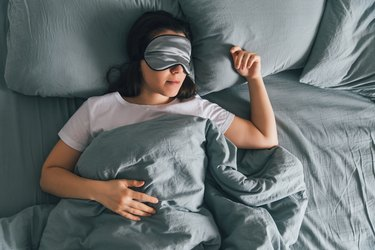 A woman sleeping in bed with an eye mask