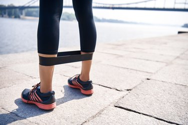 Cropped photo young sportive woman uses resistance band for exercising outdoors