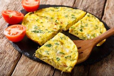 Egyptian breakfast: omelet Igga with greens, onions closeup. horizontal