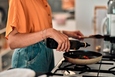 Woman in kitchen pouring oil into pan on stove
