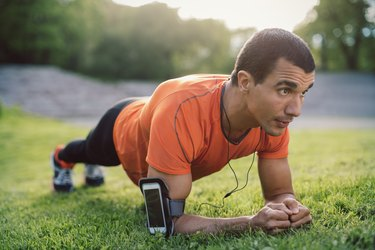 Man doing plank exercise on grassy field at park wearing smartphone armband