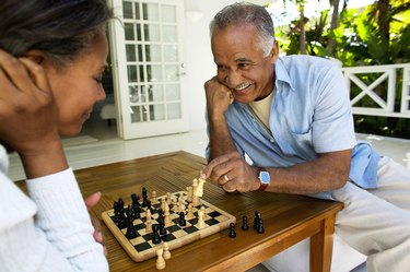A husband and wife playing chess together at home