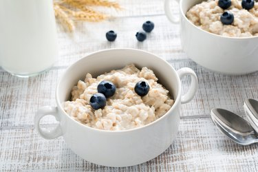 Oatmeal porridge with blueberries in white bowl
