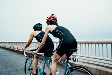Visually impaired female triathlete training together with her guide and coach on a tandem bicycle