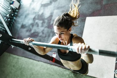 Above view of athletic woman exercising chin-ups in a gym.