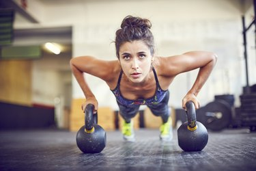 Focused athlete doing push-ups on kettlebells in gym