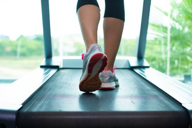 Close up womans legs in pink sneakers on a. Treadmill in the gym