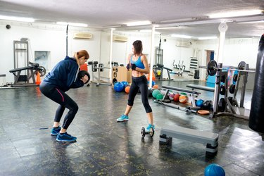 Female instructor showing her friend how to lift dumbbell