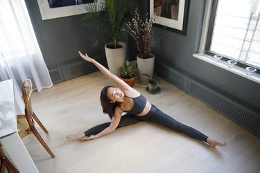 Fit Asian woman stretching in a yoga pose in an apartment setting