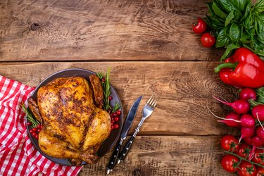 Baked chicken with herbs and vegetables for festive dinner on wooden table. Christmas, Thanksgiving Day, holidays concept. Top view