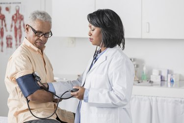 doctor taking senior patient's blood pressure