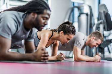 Group of athletes in a plank position at health club.