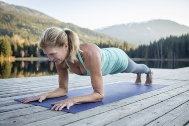 Senior woman doing plank on dock near lake during sunset.