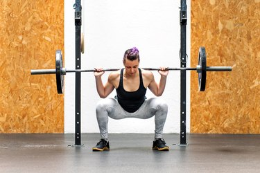 Young girl doing a back squat with a barbell