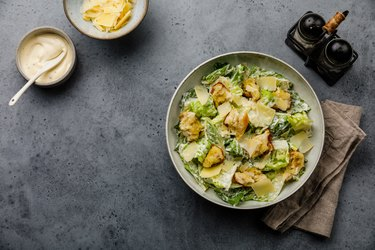 Caesar salad with croutons and parmesan cheese on concrete background copy space