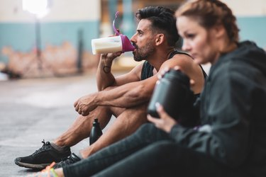 Man and woman in sports clothing drinking protein drinks