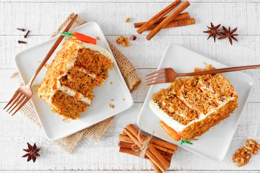 Two slices of homemade carrot cake with cream cheese frosting, top view table scene over white wood