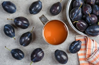 Ripe plums and plum juice in a mug on the table.