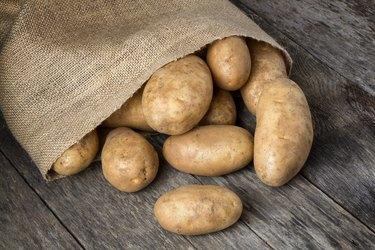 Russet Potatoes Spilling From Burlap Bag
