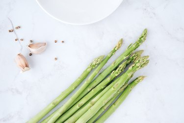 Fresh green asparagus with garlic and white peppercorns on marble table