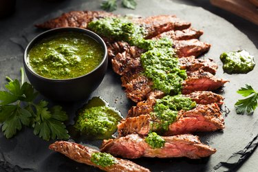 Tyrosine-rich cooked skirt steak with chimichurri on a black platter