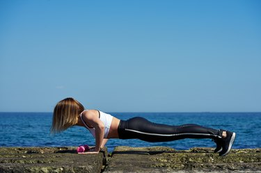 Full length of young beautiful woman in sportswear doing plank and push ups on the beach of the ocean or sea.