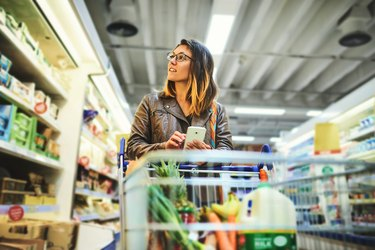 Woman shopping at grocery store with phone