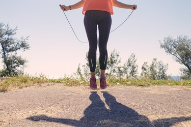 Girl in sportswear and sneakers jumping with a skipping rope