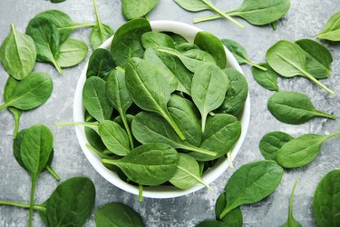Spinach leafs in bowl on grey wooden table