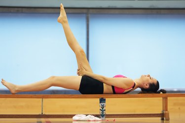 Woman laying down on bench in gym stretching