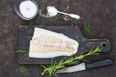Raw cod before cooking on a black chopping Board with herbs and sea salt on a dark background. Top view