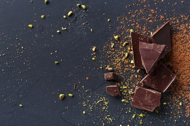 Broken chocolate pieces and cocoa powder on black background