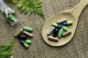 Close up of assorted capsules and pills into wooden spoon on a rustic background