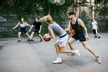 Woman playing basketball in a park preparing to pass the ball to another player.