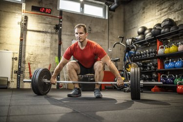 Mature strong man lifting weights at cross training in gym. Bodybuilder doing squatting with a barbell.