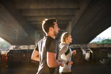 Young sporty man and woman with earphones running under the bridge outside in a city.