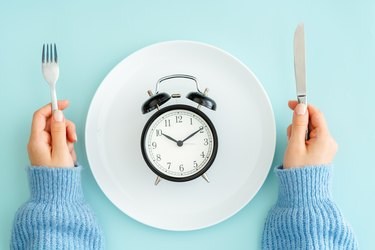 A woman holding a fork and knife next to a plate with an alarm clock to symbolize intermittent fasting