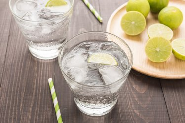 Fresh cocktail with soda, lime on a wooden background