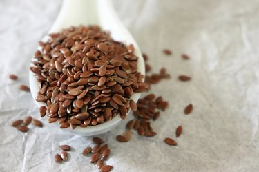 Close-up of flax seeds in a ceramic spoon on white background