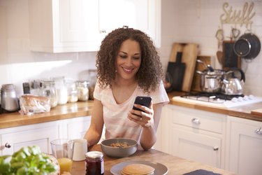 Woman Eating Breakfast Whilst Using Mobile Phone